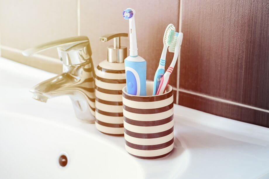 electric toothbrush and manual toothbrushes in cup by sink