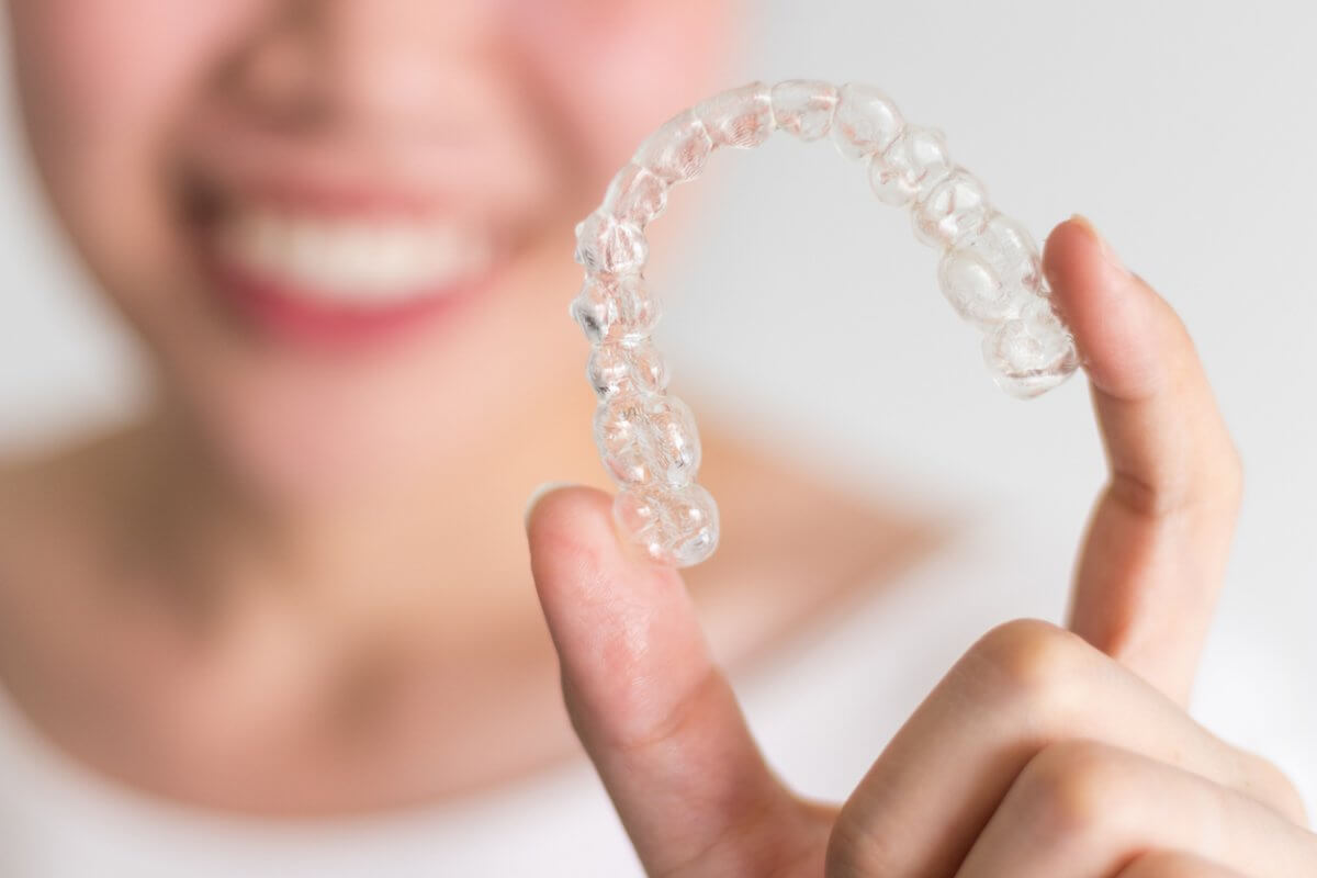 Close-up photograph of Invisalign aligners being held by a woman smiling in the background.