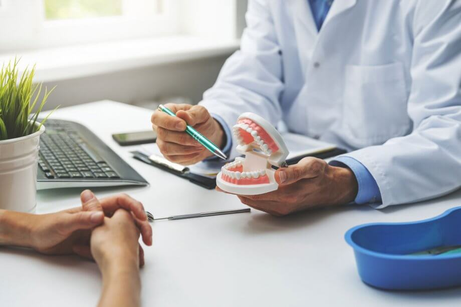 dentist talking to patient at desk pointing at model of teeth
