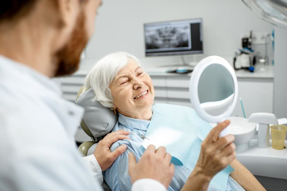 senior woman in dental exam chair holding mirror and smiling