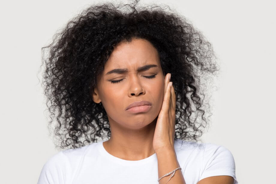 woman in pain holding left side of jaw