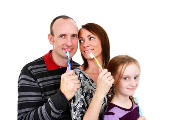Family Holding Toothbrushes