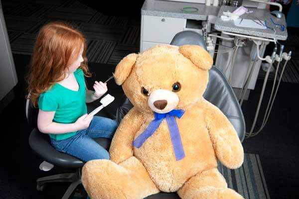 Little Girl Holding Toothbrush and Giant Teddy Bear in Dental Chair