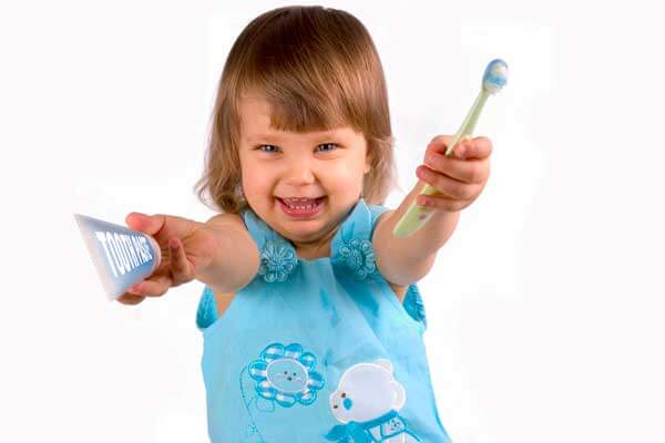 Little Girl Holding Toothbrush and Toothpaste