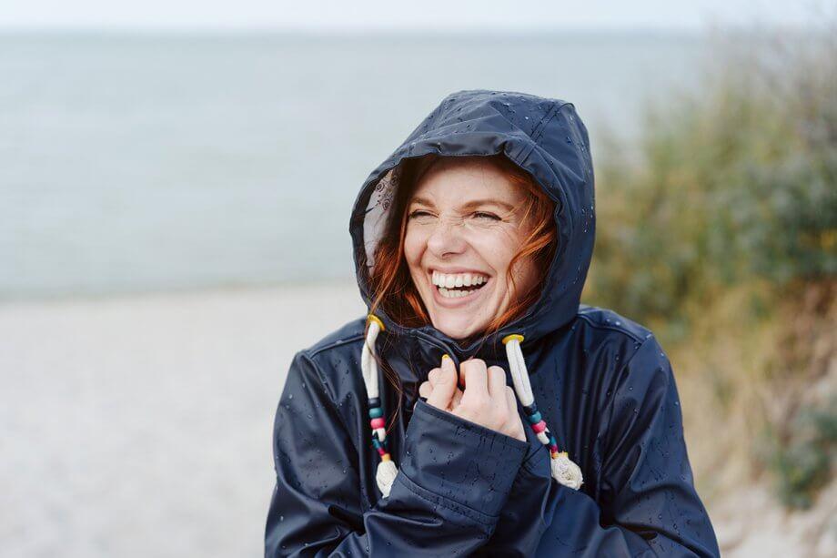 woman in dark blue rain coat smiling