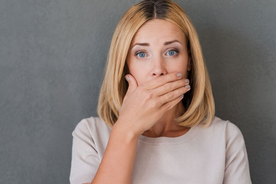 woman covering her mouth with surprised look