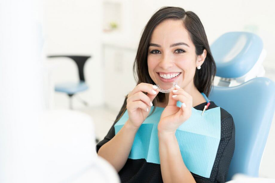 female patient in dental chair holding Invisalign appliance