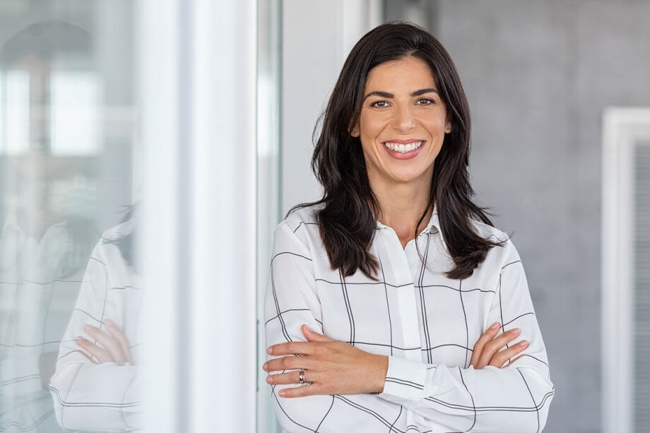 woman in white shirt standing next two glass wall