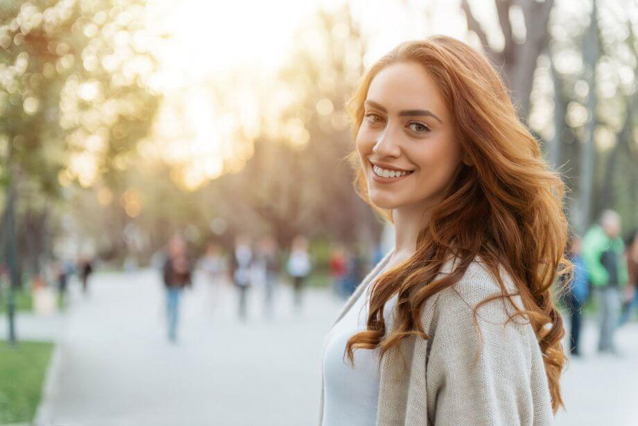 woman in park wearing beige sweater, smiling